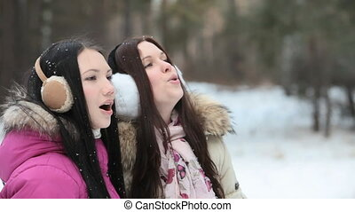 Breathing out in cold weather - Two girls playfully...