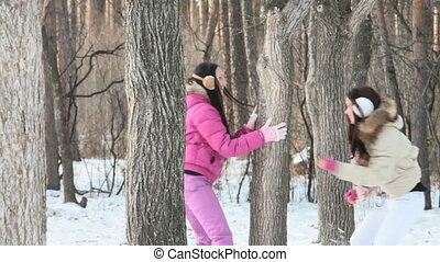 Playing in winter forest - Two cheerful girls enjoying...
