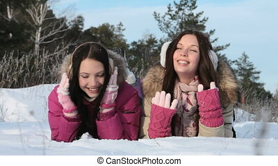 Lying in snow - Two joyful girls lying in snow