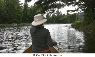 Woman paddles canoe Sunny water - Canoeing on sparkling...