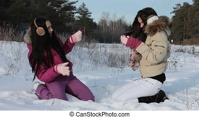 Playing in snow - Two friends playfully throwing snow at...