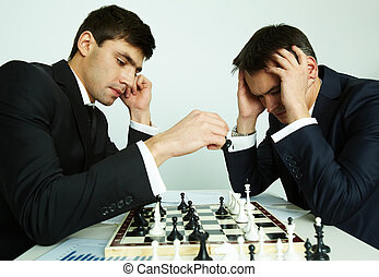 Chess battle - Image of businessman making move while...