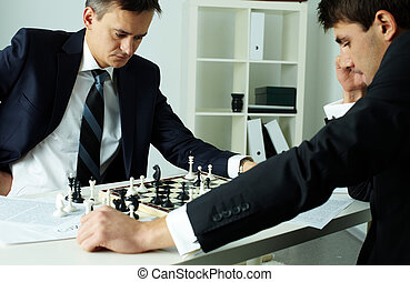 Playing business - Image of two businessmen looking at...