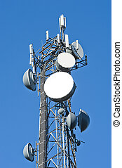 Cell tower and radio antenna against a blue sky