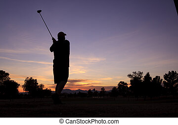 Golfer Hitting Drive at Sunset - a golfer in his follow...
