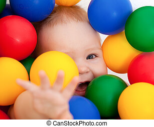 Portrait of a smiling infant lying among colorful balls -...