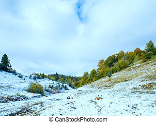 First winter snow on autumn mountain dirty road