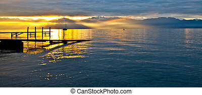 Sunrise Lake Geneva - Early morning sun trying to burst its...