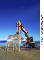 backhoe - view of a yellow backhoe  on a beach at sunrise