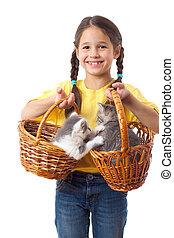 Little girl with two kittens in wicker