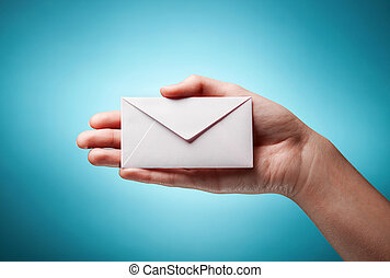womans hand holding closed envelope against blue background