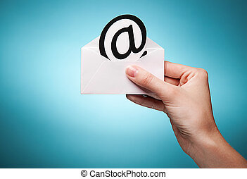 woman's hand holding an envelope with a sign of the e-mail against blue background