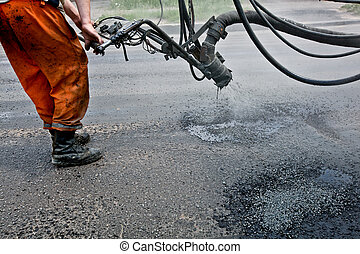 Repairing roads - Construction worker repairs holes of the...