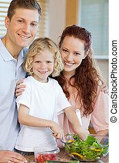 Happy family preparing salad together