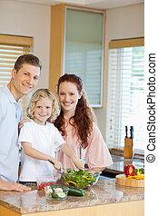 Young family preparing salad