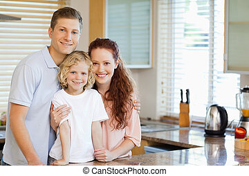 Smiling family standing behind the kitchen counter together