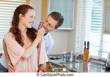 Woman giving her boyfriend some bell pepper