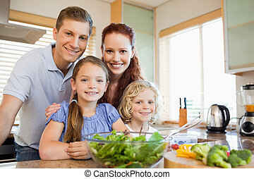Family standing behind the kitchen counter - Family standing...