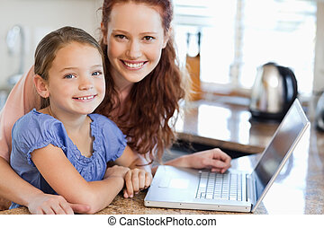 Mother and daughter with notebook in the kitchen - Mother...