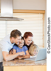 Family exploring the internet in the kitchen together