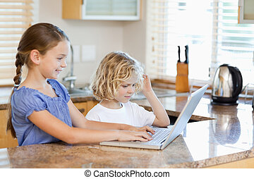 Siblings on the laptop in the kitchen - Siblings together on...