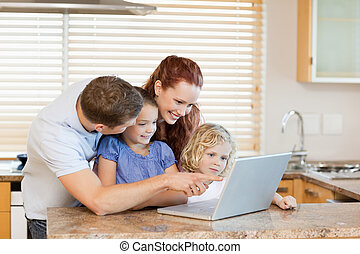 Family with laptop in the kitchen - Family together with...