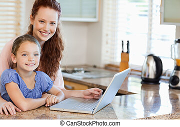 Mother and daughter surfing the internet in the kitchen -...