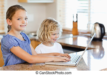 Siblings with laptop behind the kitchen counter - Siblings...
