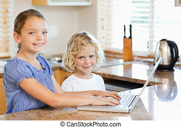 Smiling siblings on the laptop in the kitchen - Smiling...