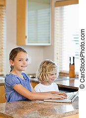 Brother and sister with laptop in the kitchen