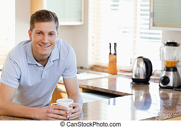 Male leaning against the kitchen counter - Smiling male...