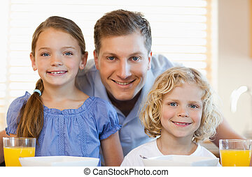 Smiling father with his children in the kitchen