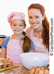 Mother and daughter with ingredients for cookies