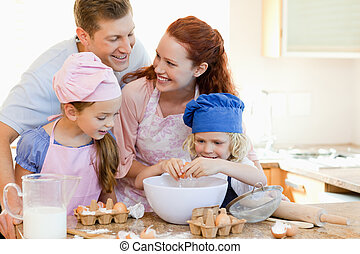 Happy family enjoys baking together - Happy young family...