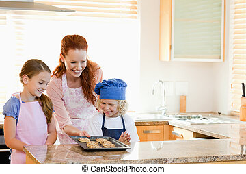 Mother presenting finished cookies to her children