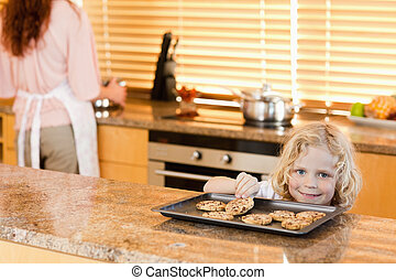 Boy stealing a cookie while his mother is not watching - boy...