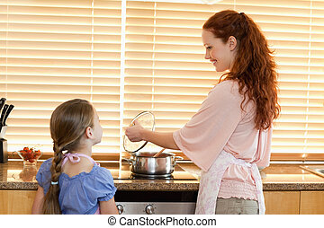 Mother showing her daughter what shes cooking - Smiling...