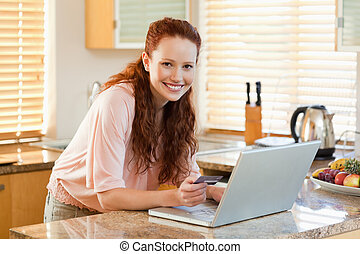Woman booking flight online in the kitchen - Happy woman...