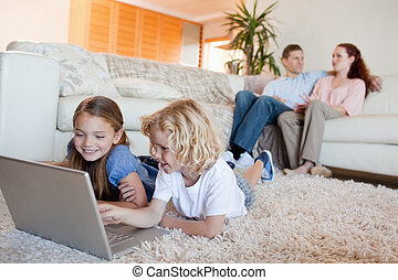 Siblings using laptop in the living room together