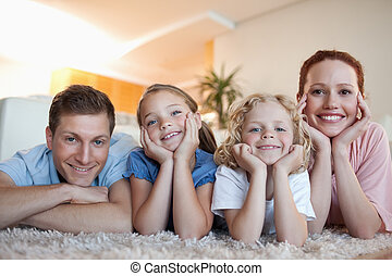 Cheerful family on the carpet - Cheerful smiling family on...