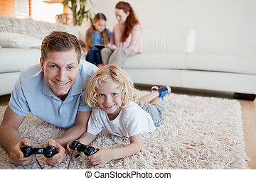 Father and son on the floor playing video games