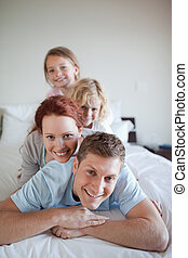 Playful family together on the bed - Playful young family...