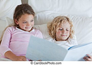 Brother and sister reading bed time story together