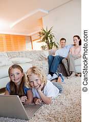 Children on the floor using laptop together