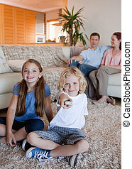 Family watching television in the living room