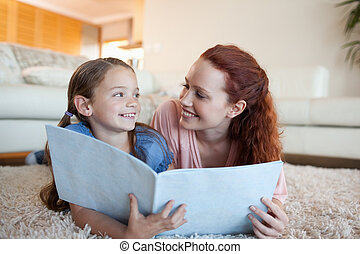 Mother and daughter with periodical on the floor - Mother...