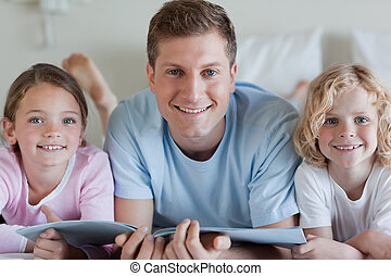 Smiling father with his children and a magazine