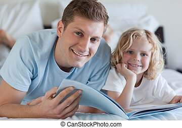 Father and son looking at magazine together