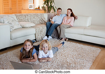 Siblings with laptop on the floor - Siblings together with...