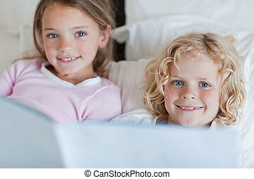 Siblings enjoy reading bed time story
